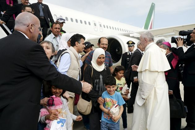 Pope Francis welcomes a group of Syrian refugees after landing at Ciampino airport in Rome following...