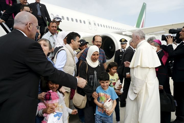 Pope Francis welcomes a group of Syrian refugees after landing at Ciampino airport in Rome following a visit at the Moria ref