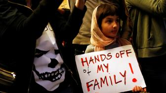 Rosalie Gurna, 9, holds a sign in support of Muslim family members as people protest against U.S. President Donald Trump's travel ban on Muslim majority countries at the International terminal at Los Angeles International Airport (LAX) in Los Angeles, California, U.S., January 28, 2017.  REUTERS/Patrick T. Fallon