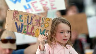 A girl holds up a sign as protesters shout at San Francisco International Airport in San Francisco, California on January 29, 2017.  US President Donald Trump issued an executive order yesterday barring citizens of seven Muslim-majority countries from entering the United States for the next 90 days and suspends the admission of all refugees for 120 days. / AFP / Josh Edelson        (Photo credit should read JOSH EDELSON/AFP/Getty Images)