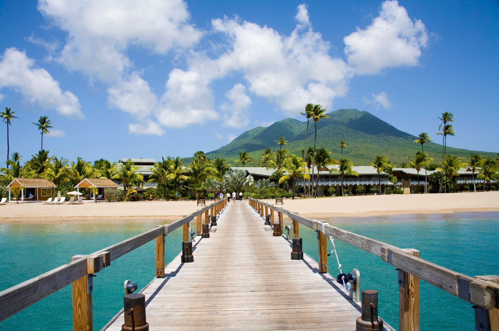Pinney's beach with tall coconut palms, and the volcano in the distance, at Nevis. Caribbean