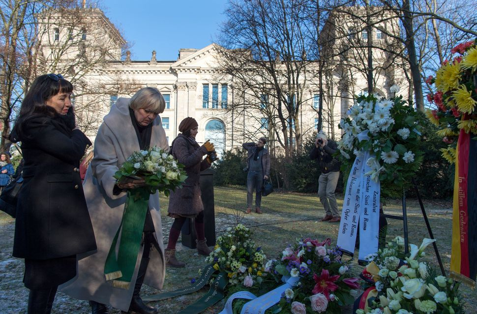 A German official lays down a wreath during a commemoration ceremony at Berlin's Roma memorial on International Holocaus