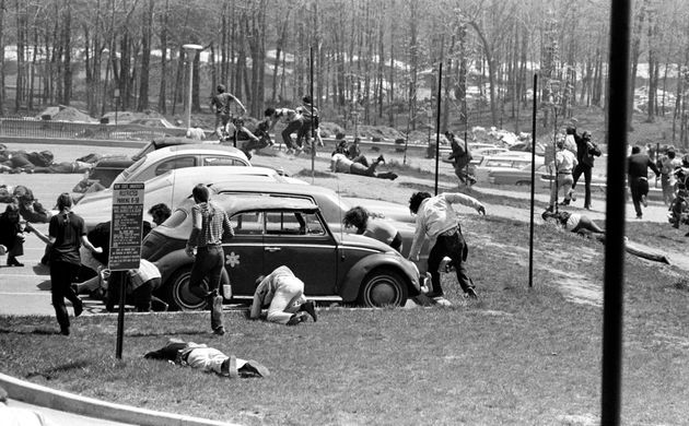 Students dive to the ground May 4, 1970, as Ohio National Guardmen open fire on faculty and students...