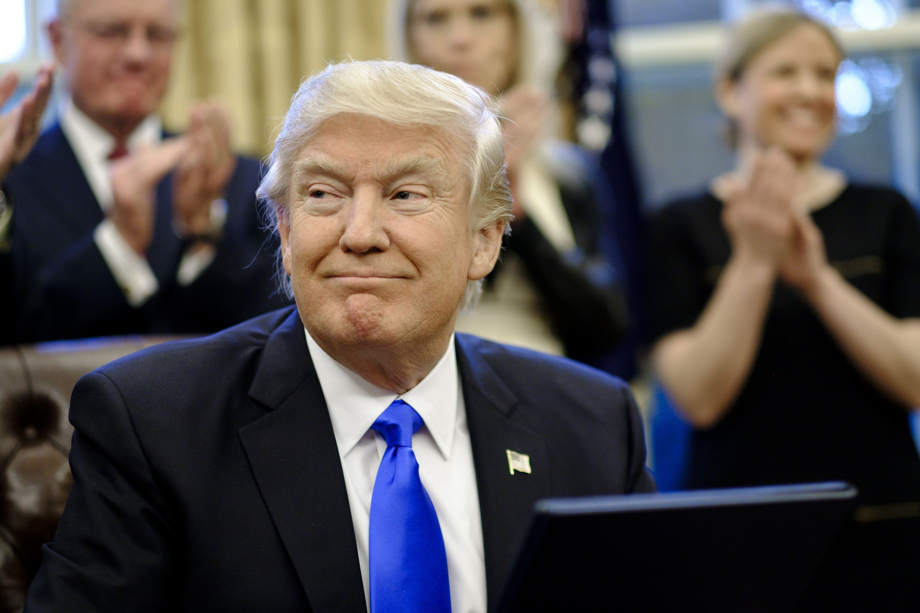 U.S. President Donald Trump smiles after signing executive orders related to a lobbying ban in the Oval Office of the White House in Washington, D.C., U.S., on Saturday, Jan. 28, 2017. Trump moved to reorganize his National Security Council, implement a lobbying ban for political appointees once they exit his administration, and order the Pentagon to create a plan to defeat the Islamic State terror organization. Photographer: Pete Marovich/Pool via Bloomberg