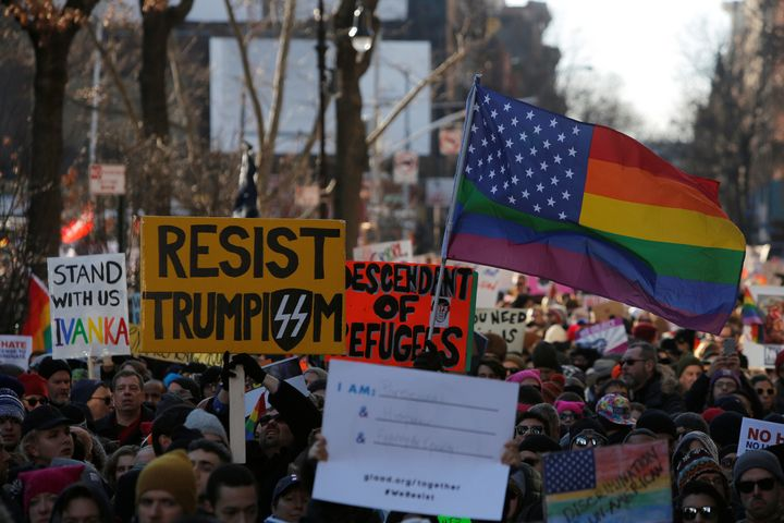 People hold signs during a gathering of the LGBTQ community and supporters protesting against U.S. president Donald Trump's a