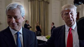 U.S. President Donald Trump stands next to Jamie Dimon, chief executive officer of JPMorgan Chase & Co., left, as he greets attendees during a Strategic and Policy Forum meeting in the State Dining Room of the White House in Washington, D.C., U.S., on Friday, Feb. 3, 2017. The gathering of the 18-member group, led by Blackstone Group LP CEO Steve Schwarzman, will give Americas first billionaire commander-in-chief a chance to reprise his Apprentice role on a grand scale. Photographer: Andrew Harrer/Bloomberg via Getty Images