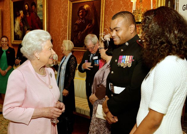 Queen Elizabeth II smiles as she talks to Lance Sergeant Johnson Beharry VC and his wife Mallissa (right)...
