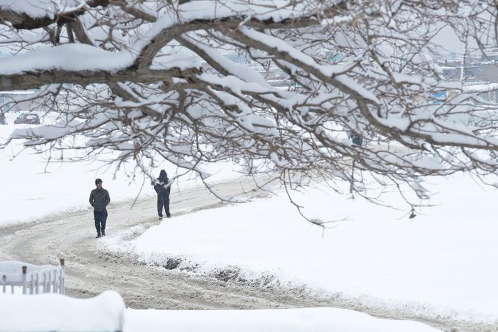 Afghan men make their way down a snow-covered street in Kabul on February 5, 2017.