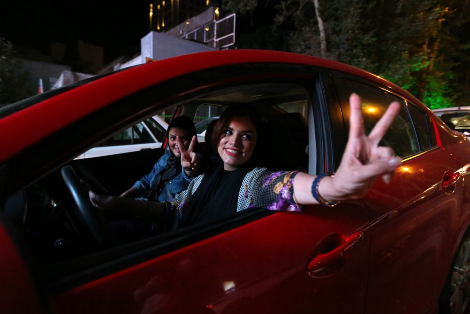 Iranian women flash the v sign for victory during celebration in northern Tehran on July 14, 2015, after Iran's nuclear negot