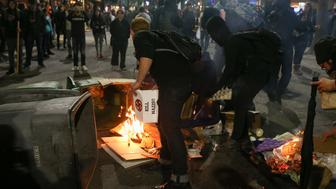 BERKELEY, CA - FEBRUARY 1: People protesting controversial Breitbart writer Milo Yiannopoulos burn trash and cardboard in the street on February 1, 2017 in Berkeley, California. A scheduled speech by Yiannopoulos was cancelled after protesters and police engaged in violent skirmishes. (Photo by Elijah Nouvelage/Getty Images)