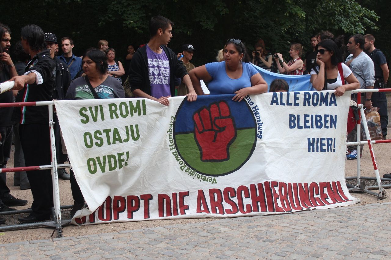 """Roma migrants in Germany carry a sign that reads """"ALL ROMA STAY HERE!"""" and """"STOP THE DEPORTATIONS!"""" during a protest."""
