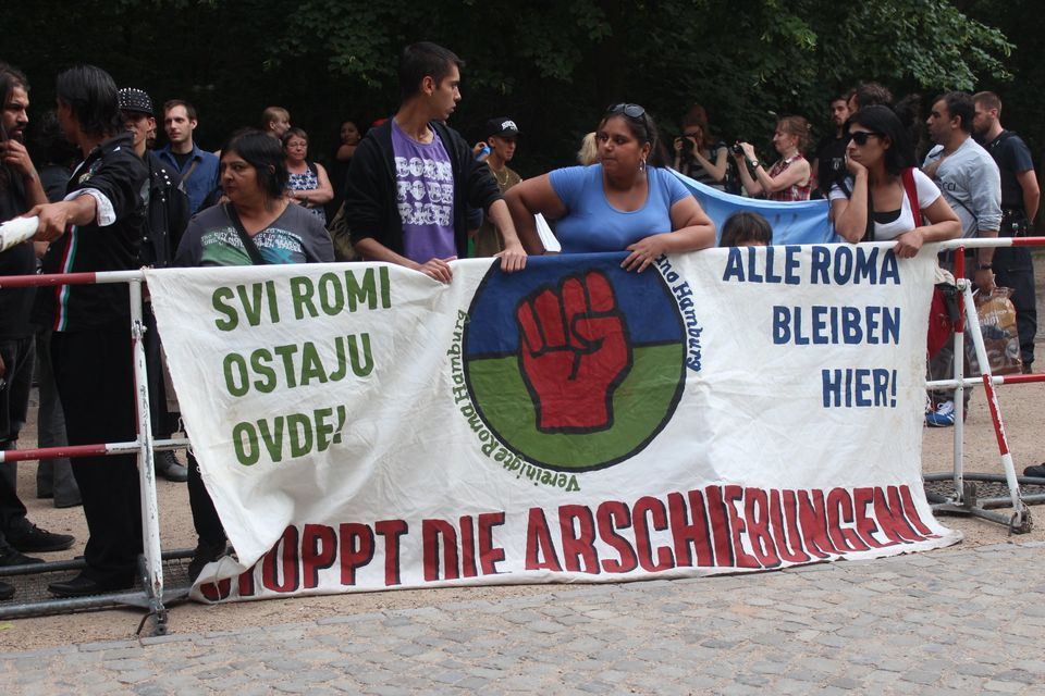 Roma migrants in Germany carry a sign that reads