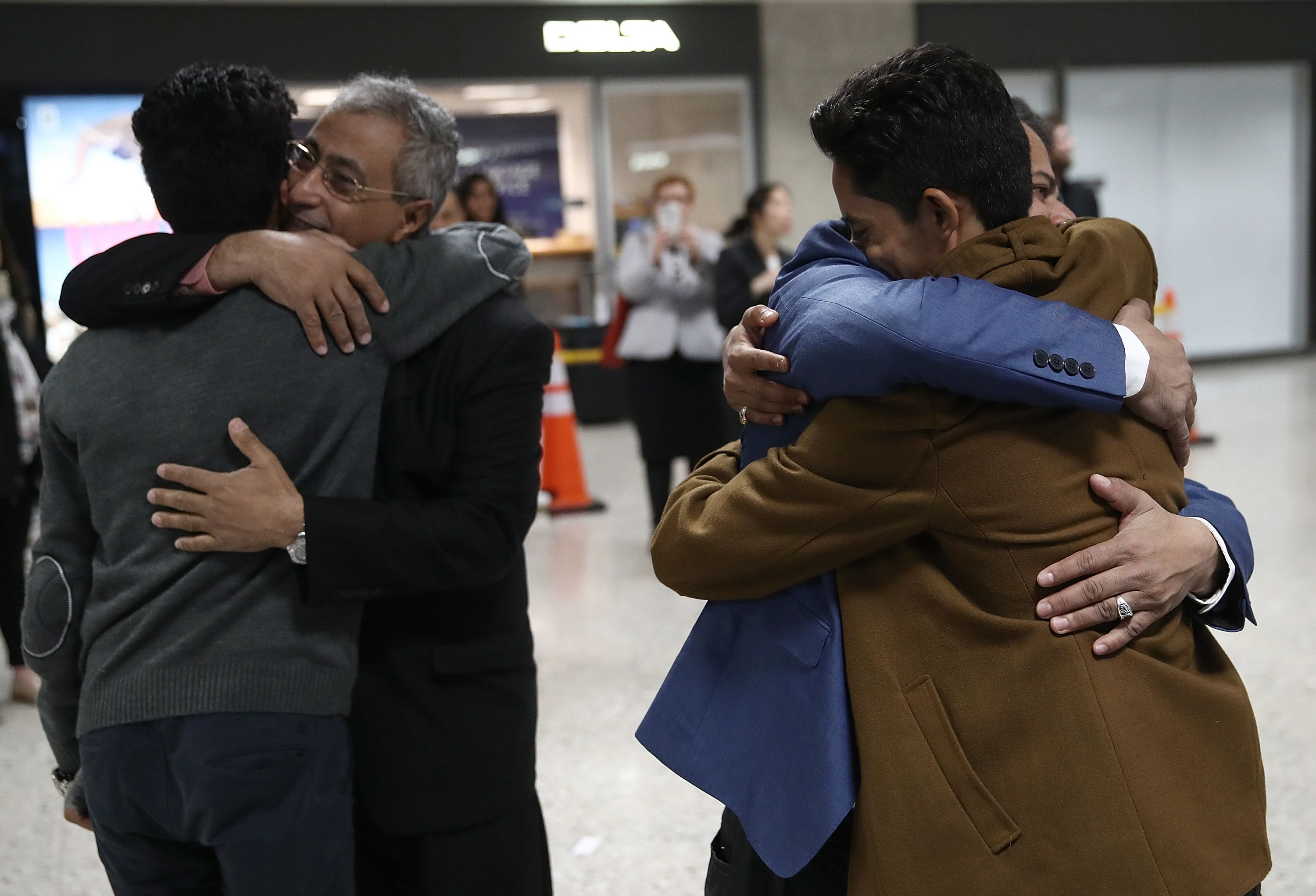 Brothers Ammar and Tareq Aqel Mohammed Aziz hug their father and uncle after arriving in Dulles International Airport.