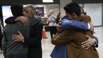 WASHINGTON, DC - FEBRUARY 06:  Ammar Aquel Mohammed Aziz (R), hugs his father Aquel (2nd R), as his brother Tareq (L) hugs his uncle Jamil Assa (2nd L) after the brothers arrived from Yemen at Dulles International airport on February 6, 2017 in Washington, DC. The brothers were prohibited from entering the U.S. a week ago due to tightened immigration policies established by the Trump administration, but were able to travel freely this week following a court injunction halting the implementation of the immigration policy.  (Photo by Win McNamee/Getty Images)