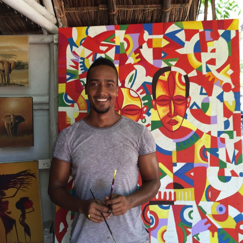 Artist Kevin Peters poses with a cubist painting he created in Diani Beach, Kenya.