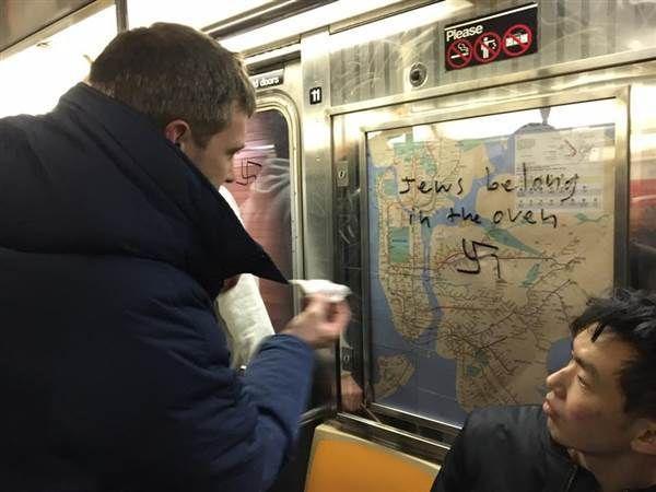 Passenger on Manhattan subway removes anti-Semitic graffiti.