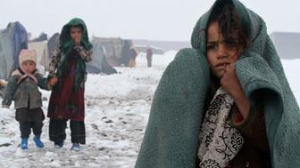 Internally displaced Afghan children stand outside their shelter in the cold at a refugee camp on the outskirts of Herat city January 20, 2015. REUTERS/ Mohammad Shoib (AFGHANISTAN - Tags: SOCIETY ENVIRONMENT)