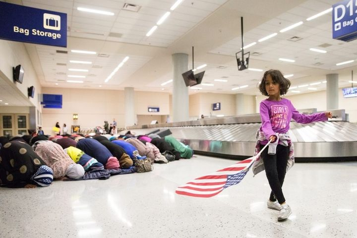 A young girl dances with an American flag while women pray behind her during a protest of the temporary travel ban .