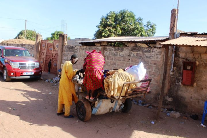 A Gambian man helps his mother onto a donkey cart as they leave a Senegalese border town and head back to their home in Gambi