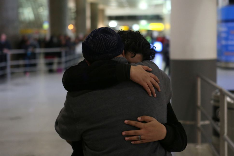 Ali Alghazali, 13, a Yemeni who was previously prevented from boarding a plane to the U.S., hugs his uncle Saleh Alghazali, u