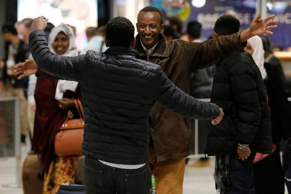 Faisal Etal, center,  a Somali national who was delayed entry to the U.S. over the travel ban, is greeted by his br