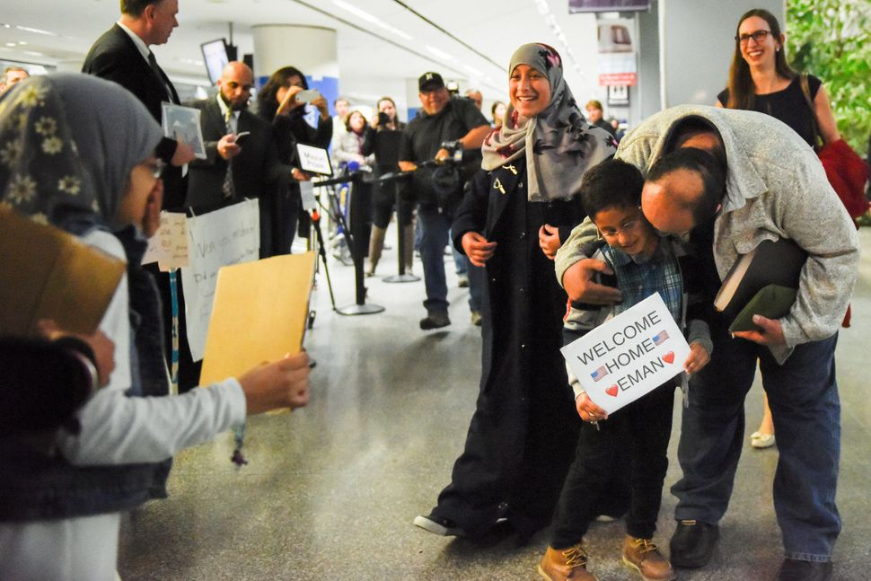 Eman Ali, 12, of Yemen,center, and her father, Ahmed Ali, arrive at San Francisco International Airport, reuniting with her f