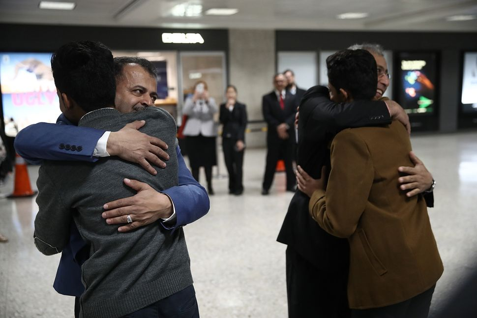 Tareq Aquel Mohammed Aziz, left, hugs his father Aquel, second left, as his brother Ammar. second right, hugs his uncle Jamil