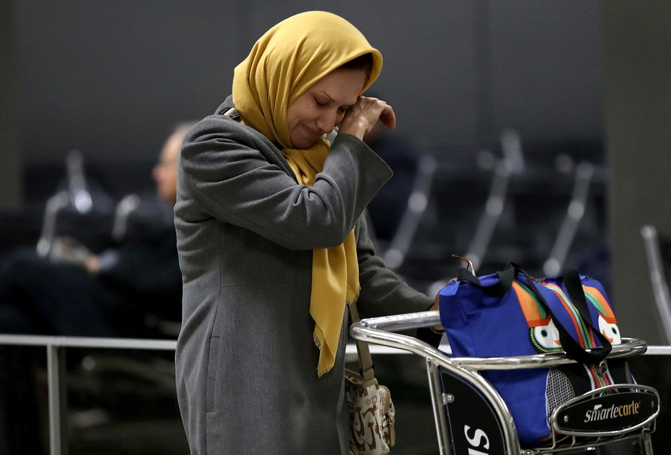 A woman traveling on a flight from Addis Ababa, Ethiopia, wipes away a tear after greeting a relative at Dulles International