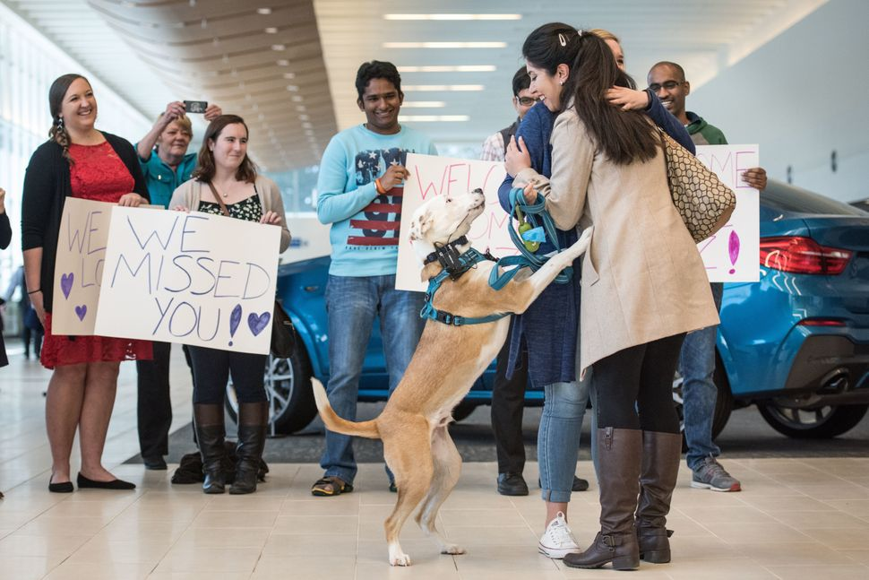 Iranian engineer Nazanin Zinouri, with her dog Dexter, gets a hug from Emma Porter after arriving at the Greenville Spartanbu