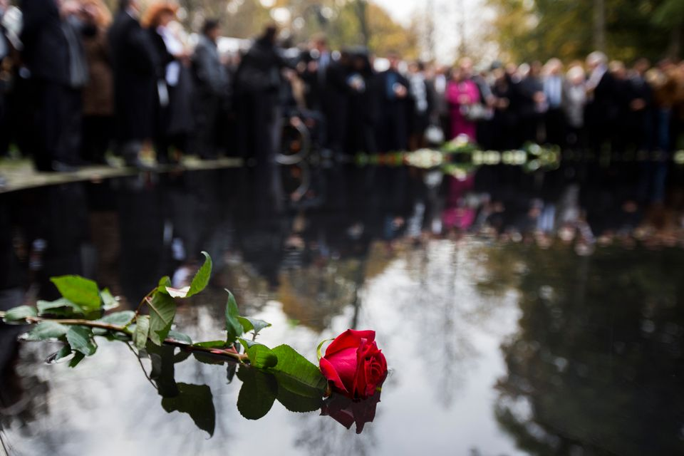 People lay flowers during the inauguration of the Memorial to the Sinti and Roma of Europe Murdered under...