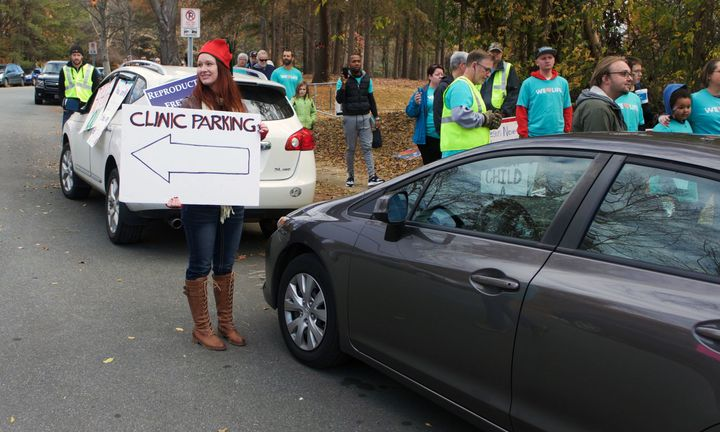 One member of Pro-Choice Charlotte directs traffic outside of APWHC in December 2016.