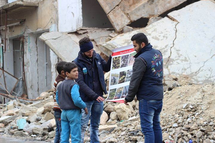 Children review manuals distributed by UNICEF-supported volunteers on the risks of unexploded remnants of war, and how to ide