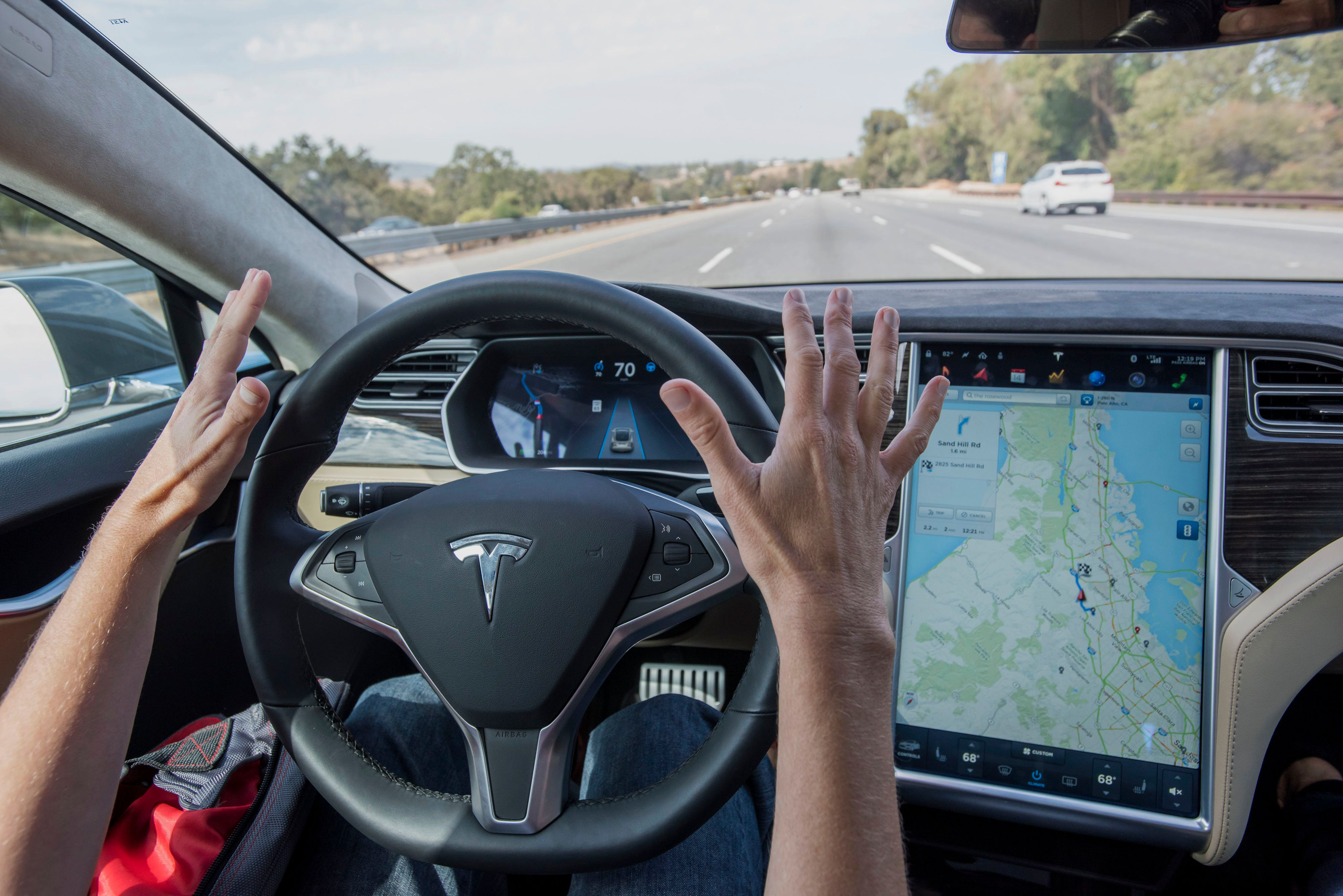 A member of the media test drives a Tesla Motors Inc. Model S car equipped with Autopilot in Palo Alto, California, U.S., on Wednesday, Oct. 14, 2015. Tesla Motors Inc. will begin rolling out the first version of its highly anticipated 'autopilot' features to owners of its all-electric Model S sedan Thursday. Autopilot is a step toward the vision of autonomous or self-driving cars, and includes features like automatic lane changing and the ability of the Model S to parallel park for you. Photographer: David Paul Morris/Bloomberg via Getty Images