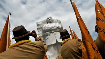 Washington, DC - August, 26: Members of the Alpha Phi Alpha fraternity, in some of the signature clothing, pass beneath a statue of Martin Luther King as they gather for a private ceremony to inaugurate the MLK memorial, on August, 26, 2011 in Washington, DC. (Photo by Bill O'Leary/The Washington Post via Getty Images)