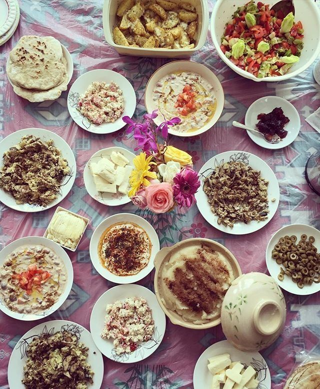 A Syrian Breakfast spread of cheese, bread, olives, fresh vegetable salad, fattet hummus, among other dishes.