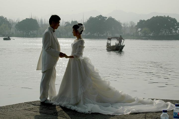 """<p><em>Hangzhou is the """"City of Love"""": a bridal couple poses for pictures on the bank of West Lake</em></p>"""