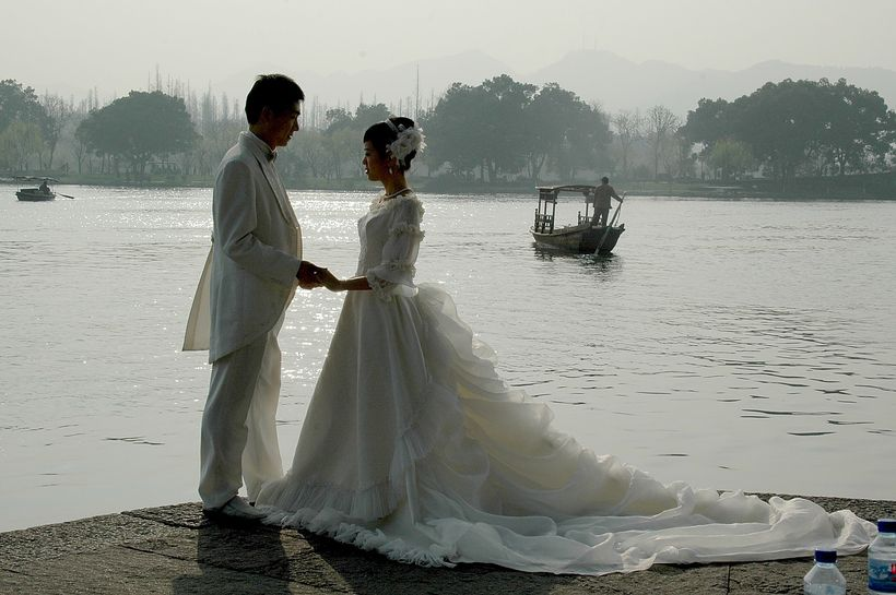 "<em>Hangzhou is the ""City of Love"": a bridal couple poses for pictures on the bank of West Lake</em>"