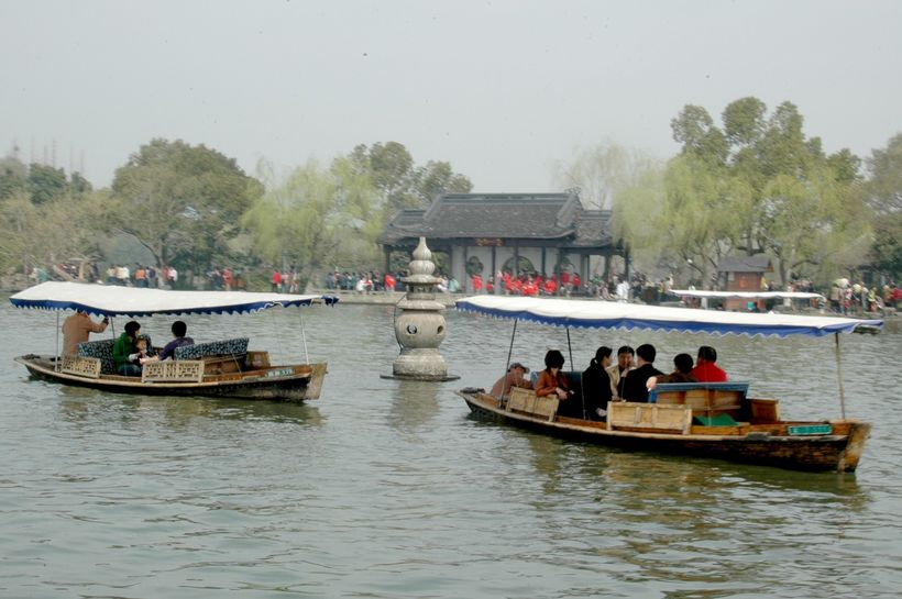<em>Traditional boats on West Lake pull up to the famous pagodas, just off Yingzhou Islet</em>