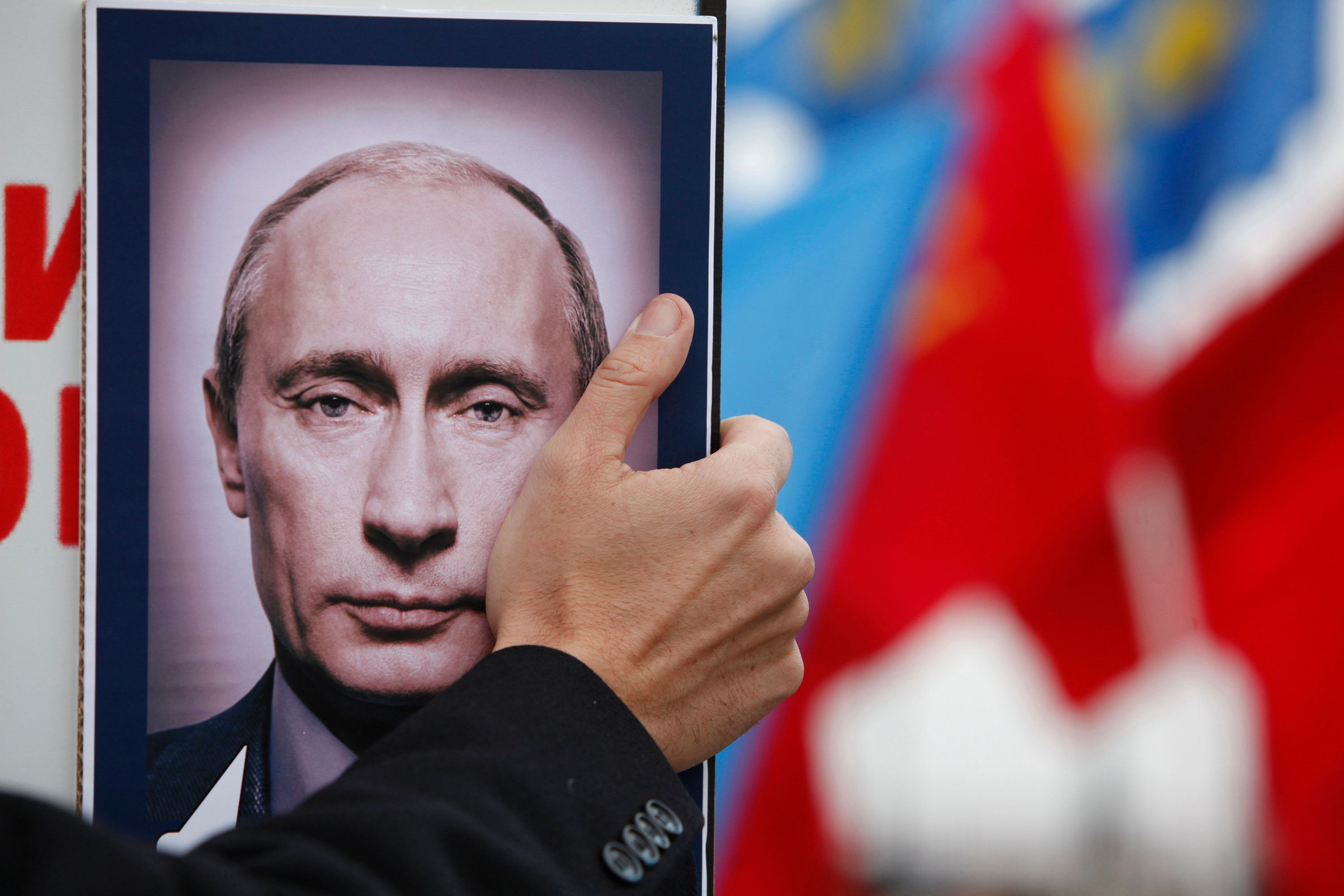 A man holds a portrait of Russia's Prime Minister Vladimir Putin during a rally to protest against violations at the parliamentary elections and the policies conducted by current Russian authorities in Russia's southern city of Stavropol, December 18, 2011. Russian Prime Minister Vladimir Putin's approval rating has dropped to its lowest level of the year in the first opinion poll published since his ruling party suffered an election setback and he faced the biggest protests of his 12-year rule. REUTERS/Eduard Korniyenko (RUSSIA - Tags: POLITICS CIVIL UNREST ELECTIONS TPX IMAGES OF THE DAY)