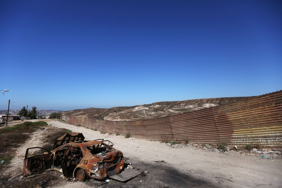 A burnt car is seen next to a section of the wall separating Mexico and the United States in Tijuana, Mexico.