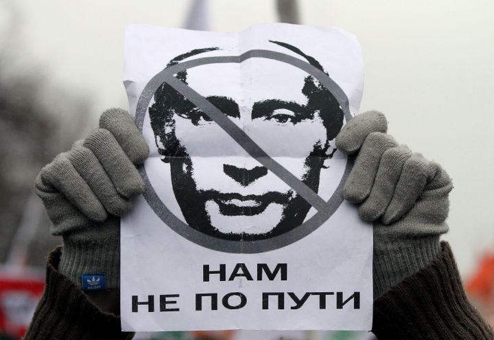 A protester holds a poster with an image of then-Russian Prime Minister Vladimir Putin reading, 'We are going different ways,