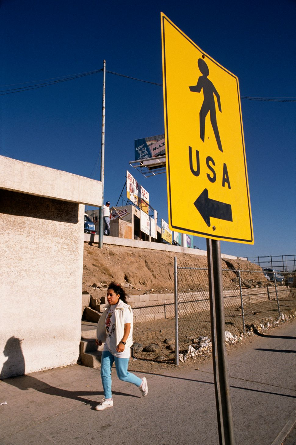 Woman walking along the America-Mexico border, near Tijuana.