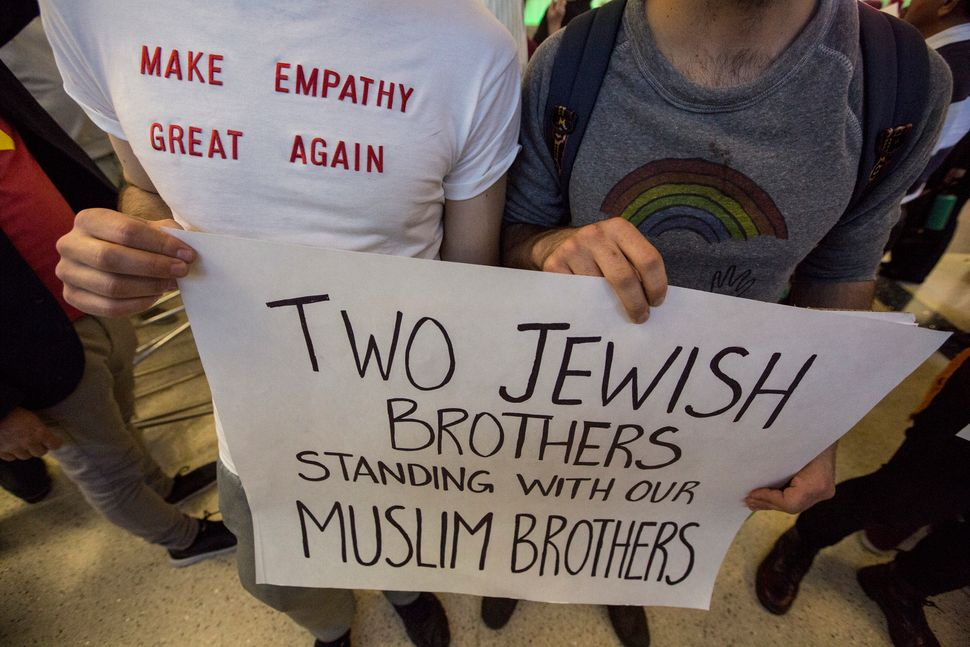 Brothers Adam, left, and Noah Reich show their support if immigrants as they join opponents of Donald Trump's new immigration