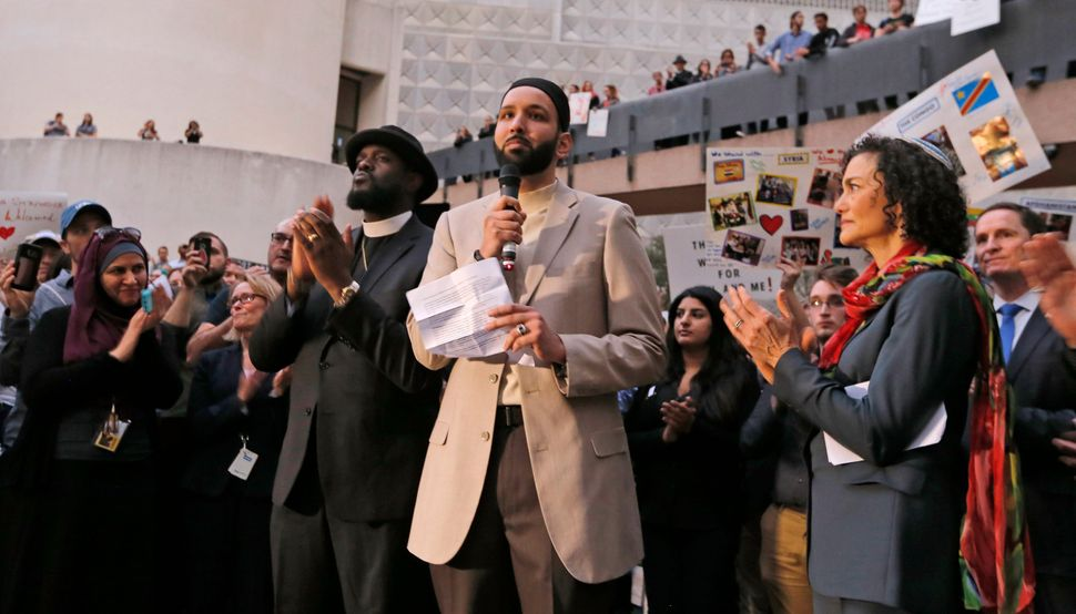 Imam Omar Suleiman speaks flanked by Dr. Michael W. Watson, left, and Rabbi Nancy Kasten, all from Faith Forward, at a vigil