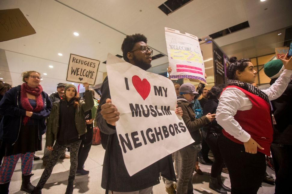 A protestor holds up a sign that reads 'I Love My Muslim Neighbors' during a demonstration against the new ban on immigration