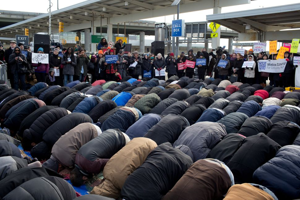 Supporters stand in the background as Muslims participate in a prayer in the parking lot of Terminal 4 at JFK International A