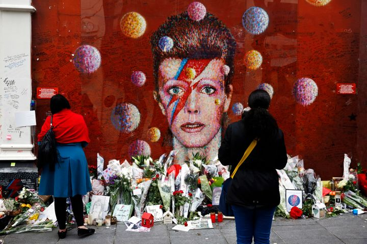 People look at a mural of David Bowie in Brixton, London.