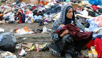 """A mother breastfeeds her baby in front of piles of rubbish at a migrant collection point in Roszke, Hungary September 11, 2015. Hungary said on Thursday it expected to finish building a fence along its border with Serbia by early October, and indicated it would call a """"state of crisis"""" next week as the right-wing government readies a clampdown on migrants and refugees streaming through the Balkans.   REUTERS/Laszlo Balogh"""