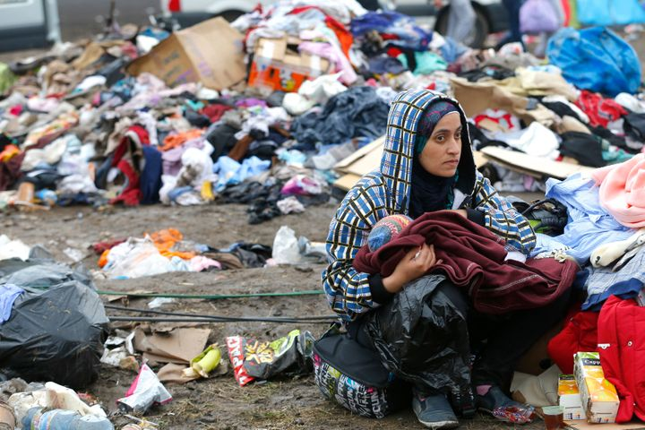 A mother breastfeeds her baby in front of piles of rubbish at a migrant collection point in Roszke, Hungary on Sept. 11, 2015