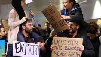Meryem Yildirim, 7, left, sits on her father, Fatih, of Schaumburg, and Adin Bendat-Appell, 9, right, sits on his father, Rabbi Jordan Bendat-Appell, of Deerfield, during a protest on Monday, Jan. 30, 2017 at O'Hare International Airport in Chicago, Ill. (Nuccio DiNuzzo/Chicago Tribune/TNS via Getty Images)